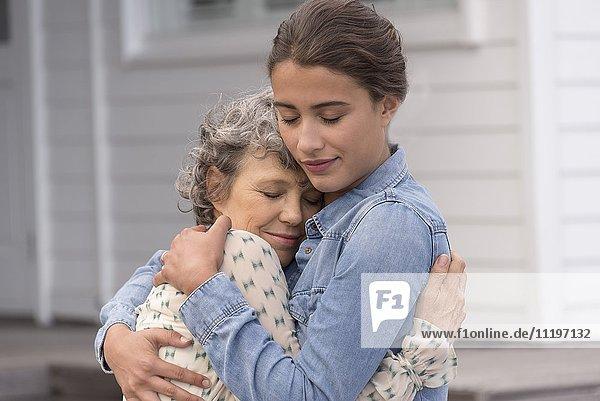 Liebevolle Mutter umarmt ihre kleine Tochter.
