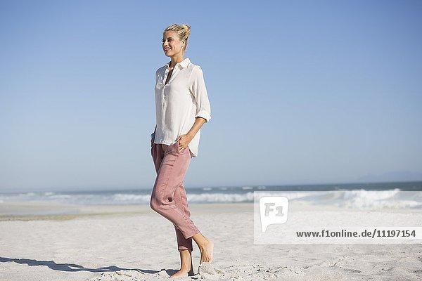 Schöne junge Frau  die am sonnigen Strand spazieren geht