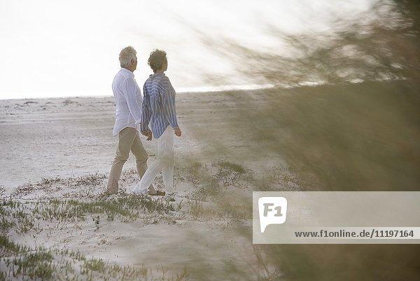 Fröhliches Senior-Paar beim Spaziergang am Strand