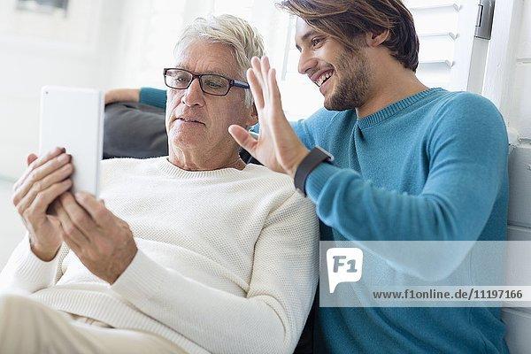 Vater und Sohn mit digitalem Tablett im Wohnzimmer