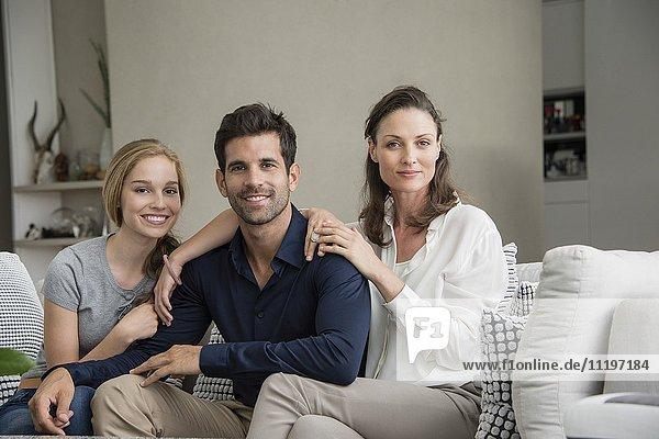 Porträt einer glücklichen Familie  die auf einer Couch sitzt.