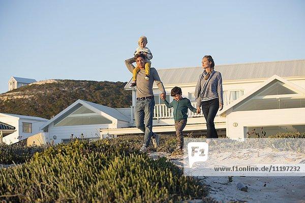 Pärchen mit ihren Kindern  die am Strand spazieren gehen.