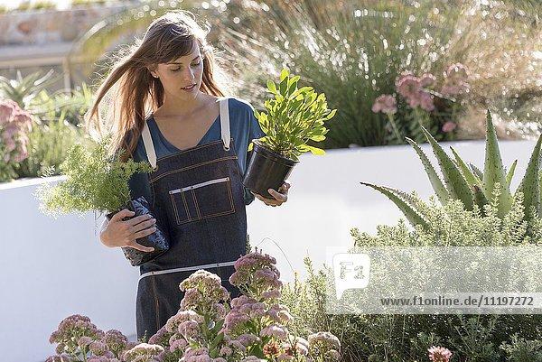 Schöne junge Frau bei der Gartenarbeit