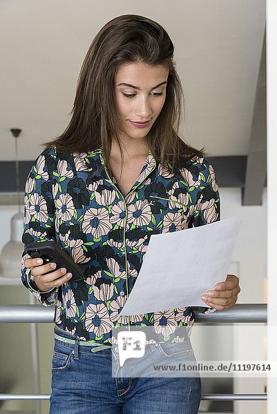 Beautiful young woman reviewing a document and using a mobile phone