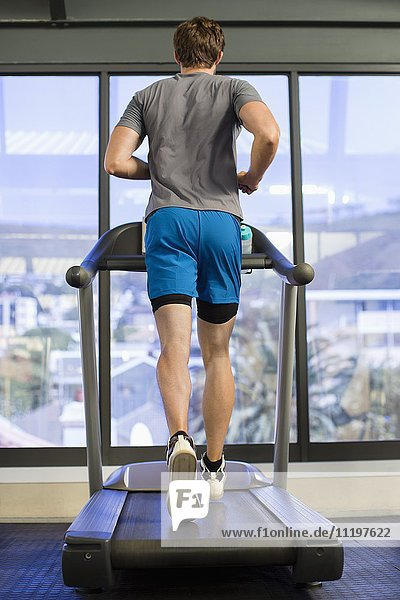 Rear view of a man running on a treadmill