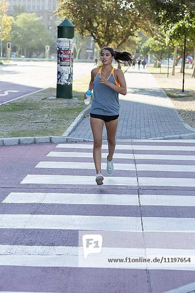Young female athlete running in a park