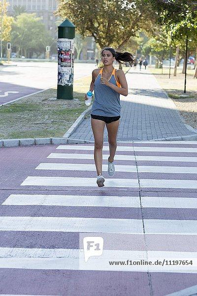 Junge Sportlerin beim Laufen im Park