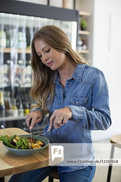 Glückliche Frau beim Mittagessen im Restaurant
