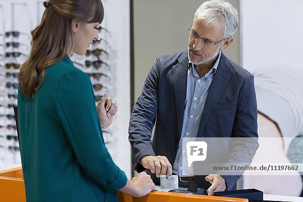 Young woman paying with credit card in optical shop