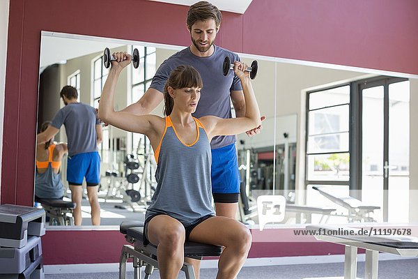 Male instructor helping a woman to lifting dumbbells