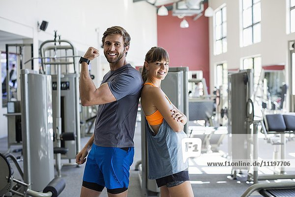 Happy couple standing back to back in a health club