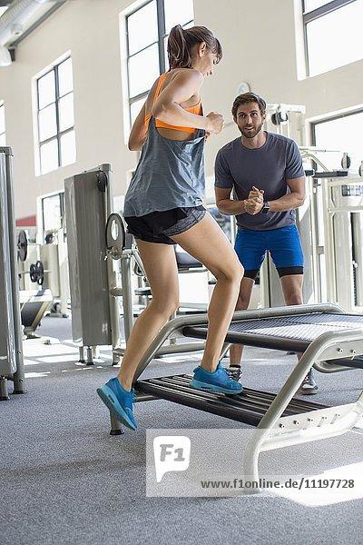 Trainer hilft einer Frau beim Training in einem Fitnessclub