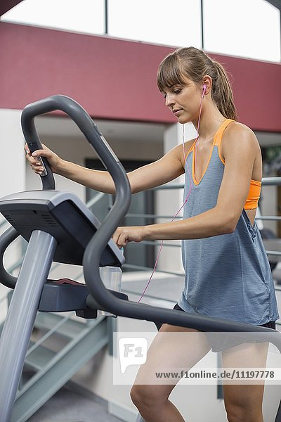 Young woman exercising on a machine in a fitness club