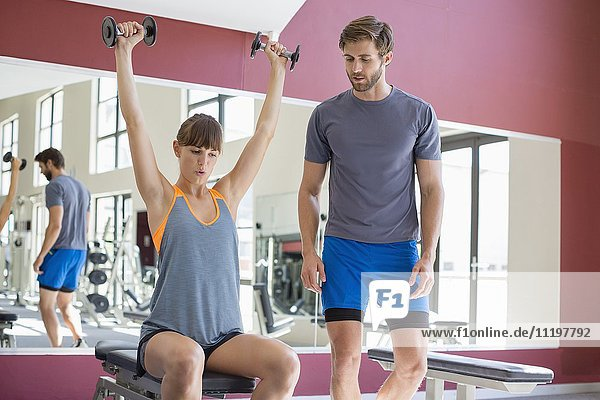 Trainer looking at a young woman lifting dumbbells in a gym