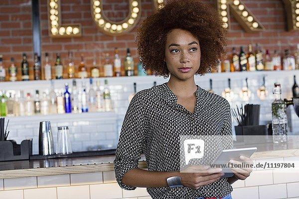Junge Frau mit einem digitalen Tablett an der Theke