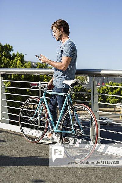 Junger Mann mit Handy und Fahrrad im Freien