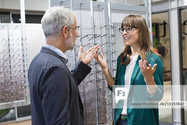 Verkäufer im Gespräch mit dem Kunden im optischen Geschäft