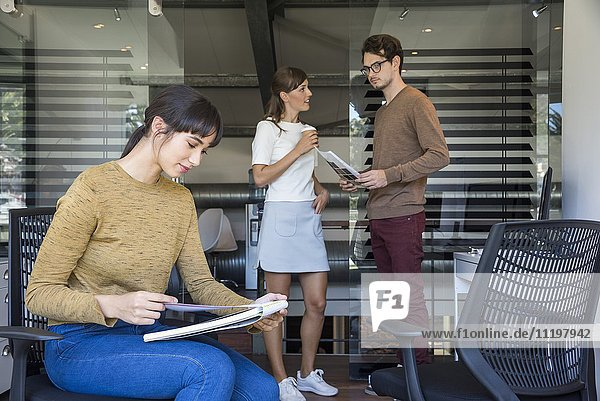 Businesswoman reading a file with her colleagues in the background