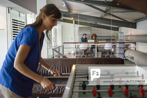 Junge Frau macht Pause beim Tischfußball im Büro