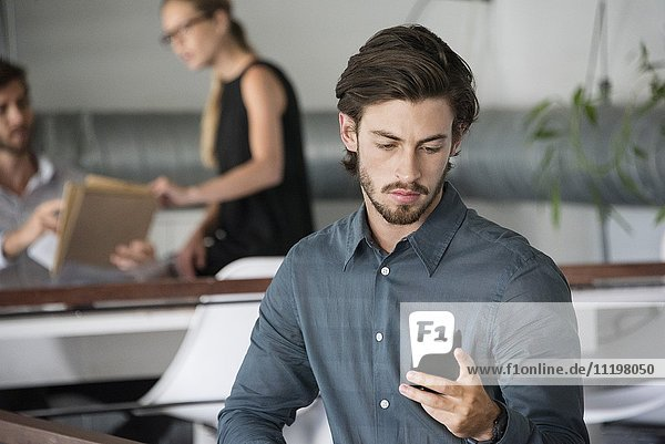 Businessman using a smart phone with his colleagues in the background