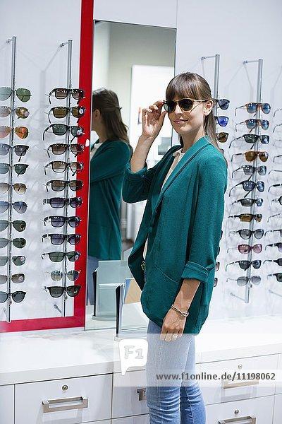 Fröhliche junge Frau beim Anprobieren der Sonnenbrille im Optikergeschäft