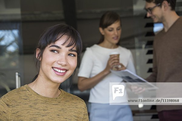 Close-up of a beautiful businesswoman smiling with her colleagues in the background