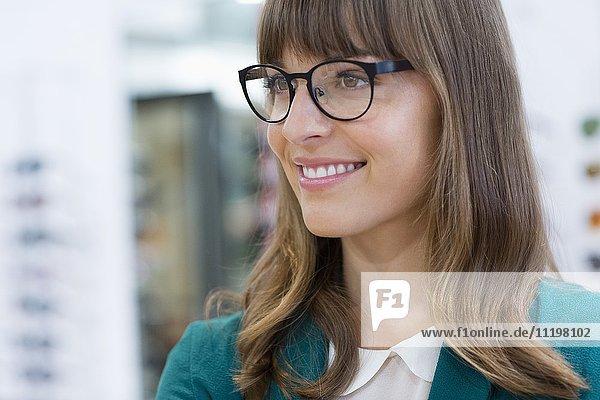Glückliche junge Geschäftsfrau lächelt im Büro