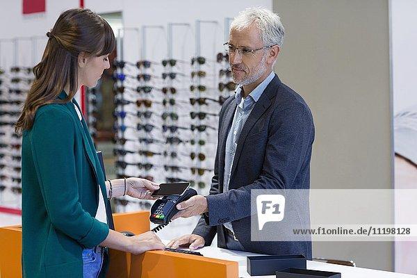 Junge Frau bezahlt mit Kreditkarte im Optikergeschäft