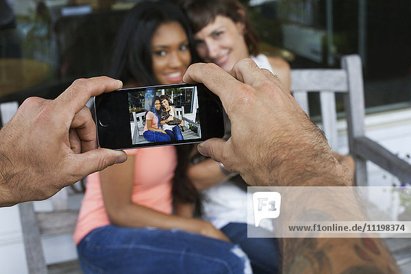 Man photographing women with cell phone