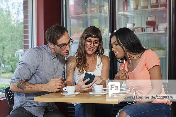 Friends texting on cell phone in coffee shop