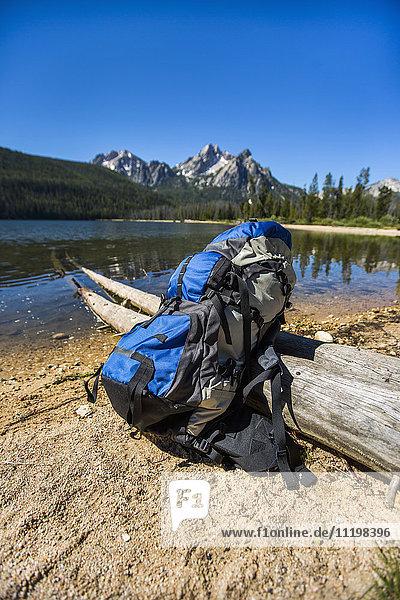 Backpack leaning on log near river