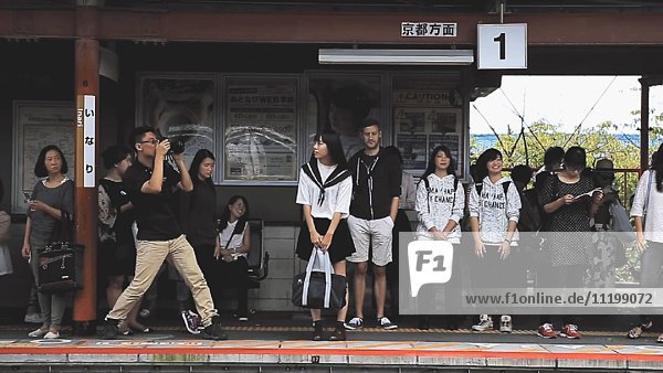 Man Taking Photo of Group of People on Train Platform