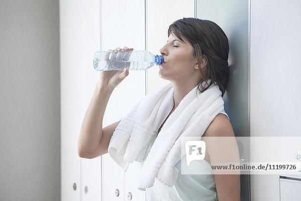 Frau trinkt Flaschenwasser in der Umkleidekabine
