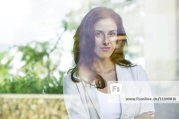 Geschäftsfrau schaut aus dem Fenster aus dem Büro