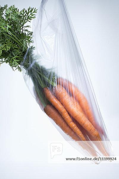 Fresh carrots in plastic bag over white background