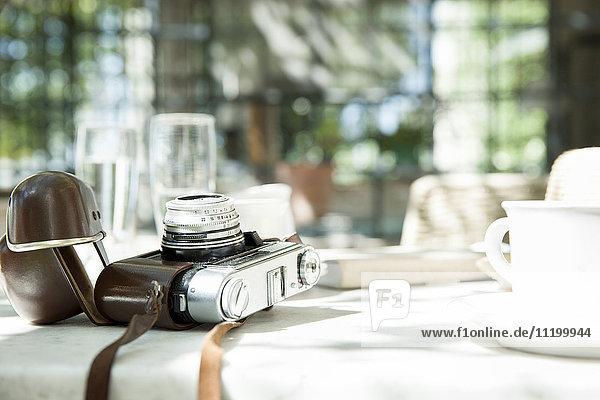Kamera und Tasse mit Untertasse auf dem Tisch