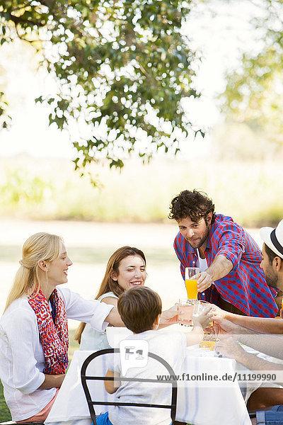 Freunde  die beim gemeinsamen Essen im Freien anstoßen