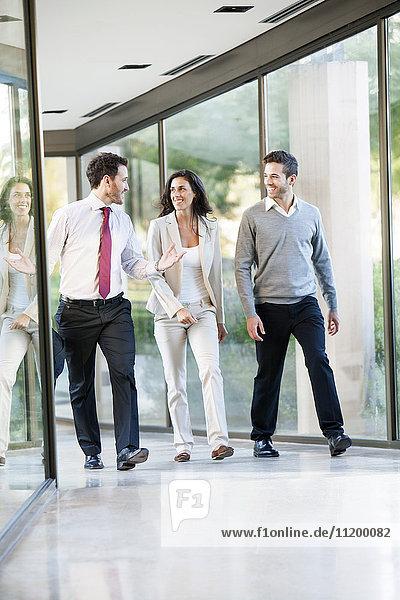 Geschäftsmann im Spaziergang und im Gespräch mit Mitarbeitern