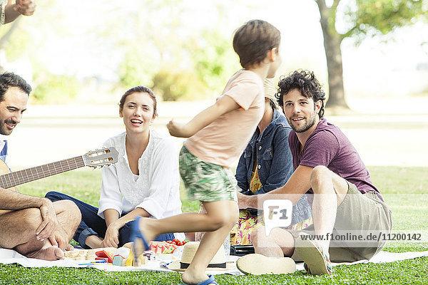 Familie genießt Picknick im Park  Junge rennt herum