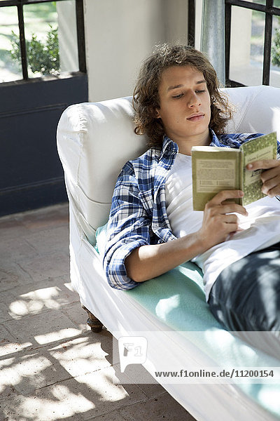 Junger Mann liest Buch auf der Couch