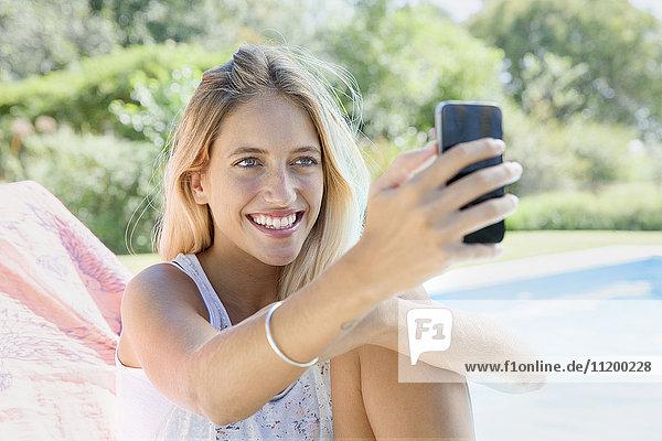 Frau mit Smartphone am Pool
