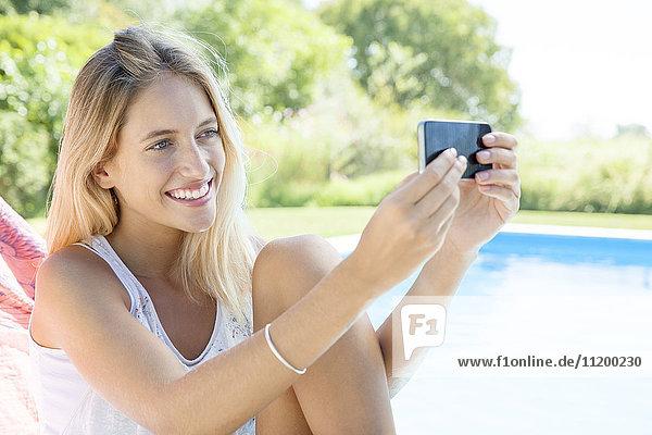 Frau  die einen Selfie am Pool mit dem Smartphone nimmt