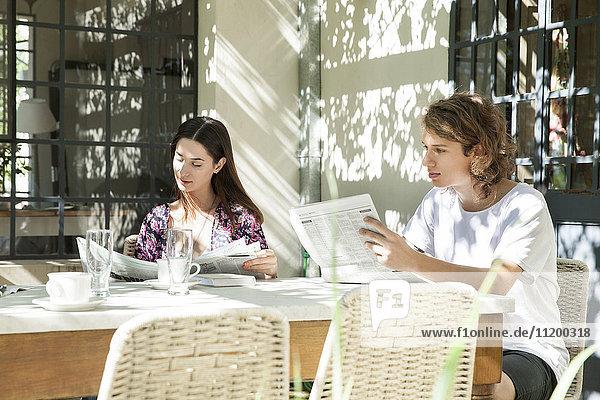 Junges Paar beim Zeitungslesen beim Frühstück im Garten