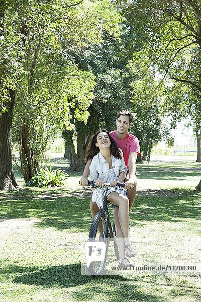 Junges Paar beim Radfahren zusammen mit der Freundin sitzend im Damensattel auf der Querlatte