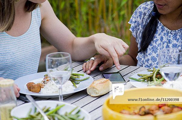 Frauen beim gemeinsamen Essen im Freien auf das Smartphone schauen