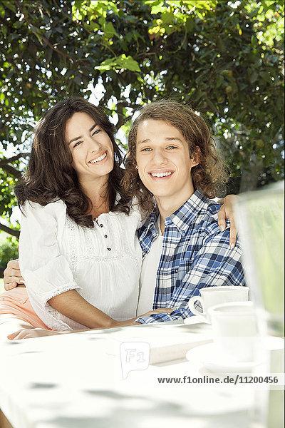 Junges Paar am Frühstückstisch im Freien