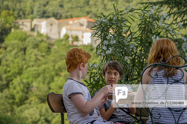 Children playing card game outdoors