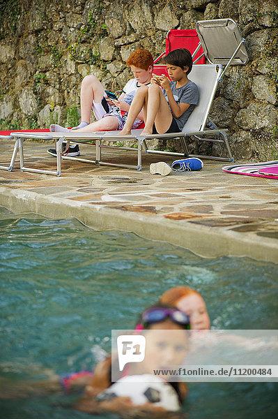 Jungen spielen Handheld-Videospiele neben dem Schwimmbad
