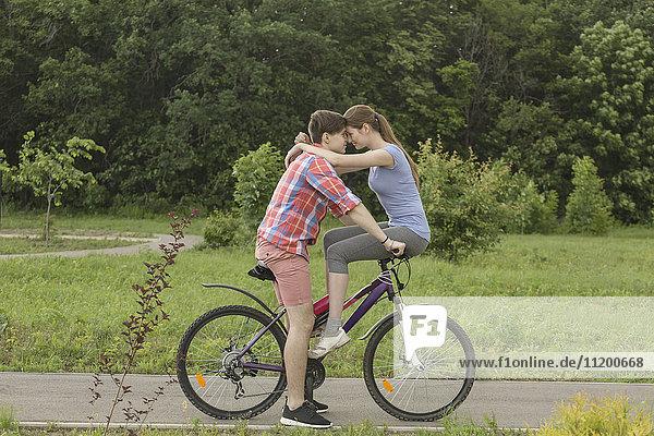 Romantisches Paar auf dem Fahrrad gegen Bäume im Park sitzend