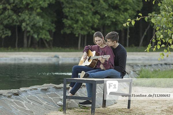 Liebender Mann  der sich mit seiner Freundin auf der Parkbank am See ausruht.